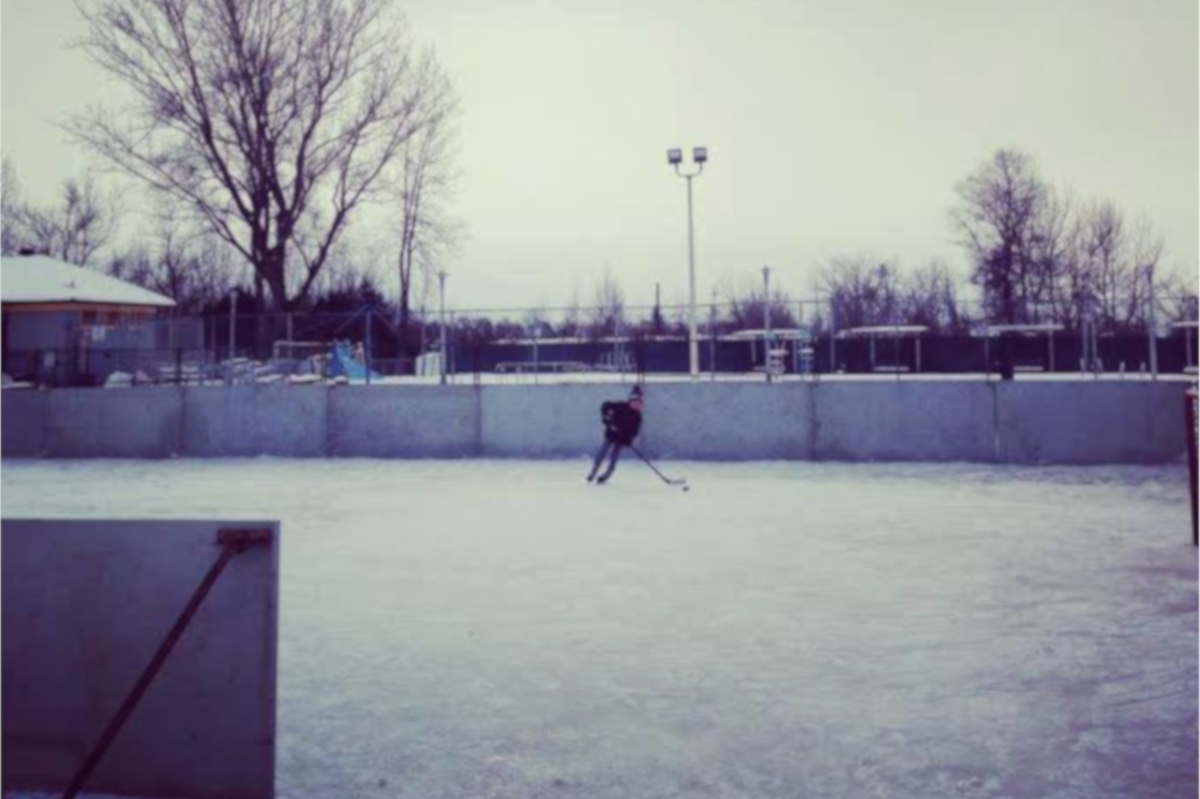 young boy playing hockey on the outdoor rink